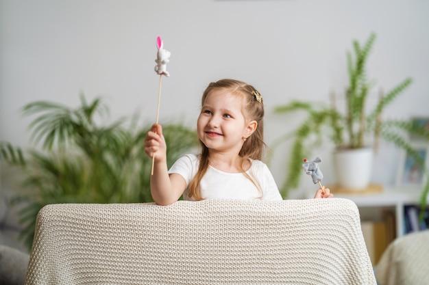 Petite fille joue au théâtre. marionnettes à doigt habillées sur des bâtons tenus par un enfant