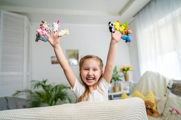 Petite fille joue au théâtre. des marionnettes à doigt sont posées sur les mains des enfants.