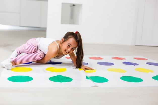 Petite fille joue au twister à la maison
