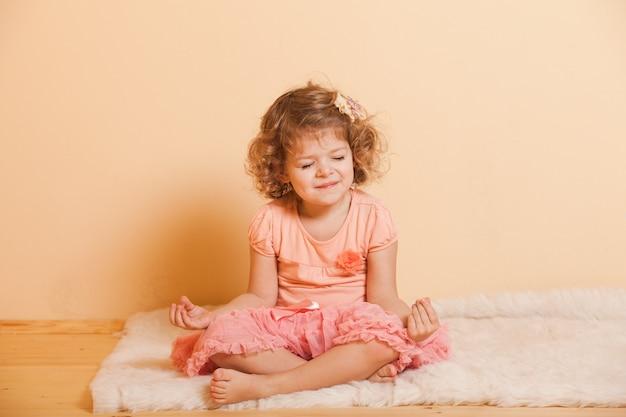 La petite fille joue au yoga à la maison