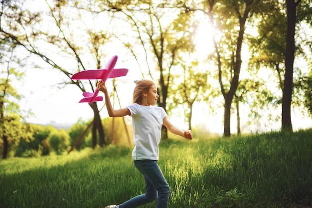 Petite fille, joue avec un avion jouet en l'air dans le parc.