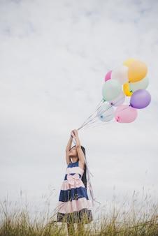 Une petite fille joue avec des ballons sur un champ de prairies.