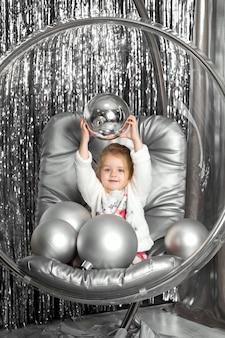 Petite fille joue sur une chaise un bol en verre avec des boules d'argent. couverture de la reine des neiges.