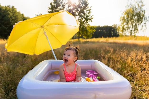 Petite fille joue dans la piscine gonflable.