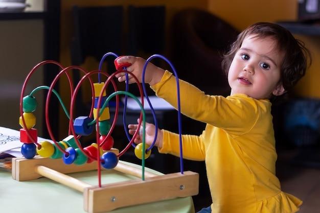 Une petite fille joue avec un jeu éducatif de cubes et de boules en bois