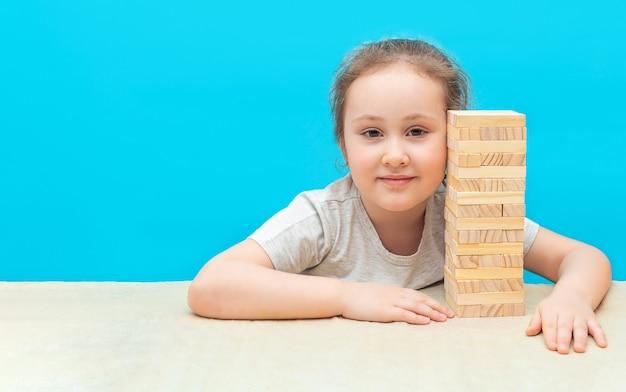 Une petite fille joue à un jeu de société fait de blocs de bois