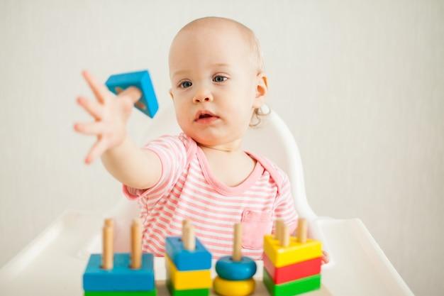 Petite fille joue avec un jouet éducatif - une pyramide en bois multicolore. développement de l'amende