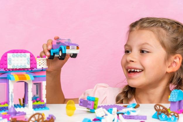 Une petite fille joue un kit de construction sur une table rose.