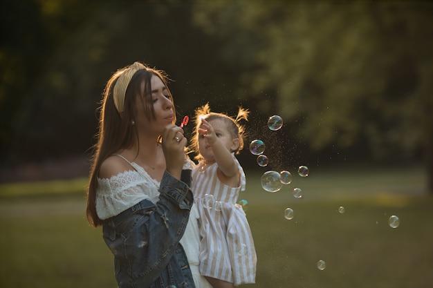 Petite fille joue avec maman dans la nature