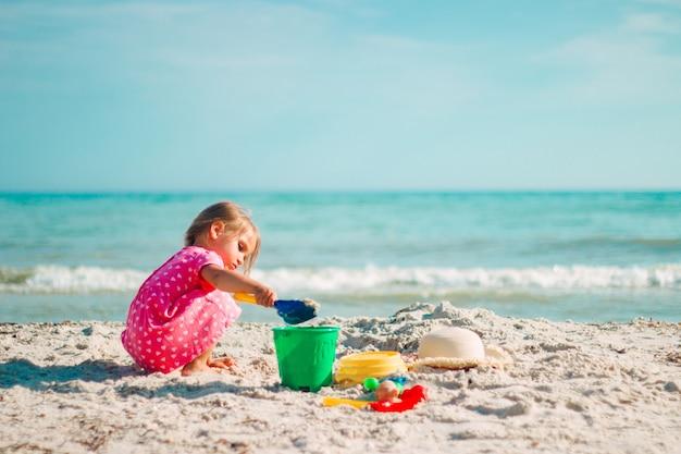 Une petite fille joue avec une omoplate et un seau sur la plage dans une robe coeur rose