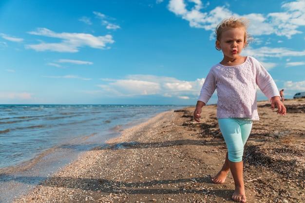 Petite fille joue près de la mer