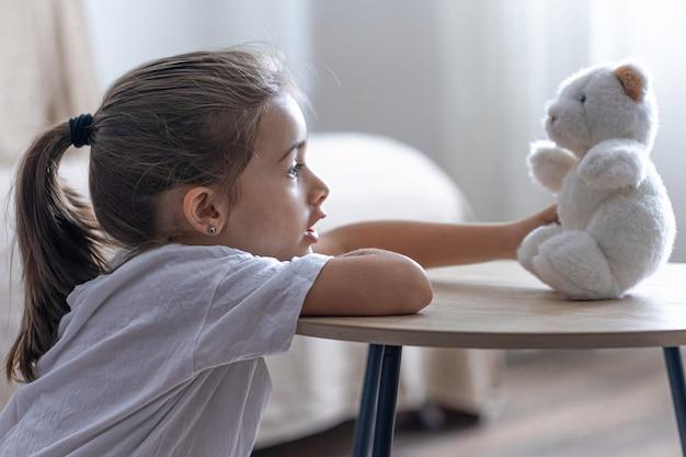 Une petite fille joue avec son ours en peluche.
