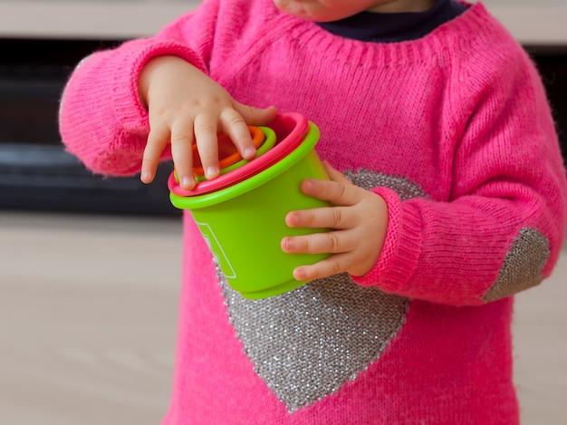 Petite fille joue avec des tasses colorées