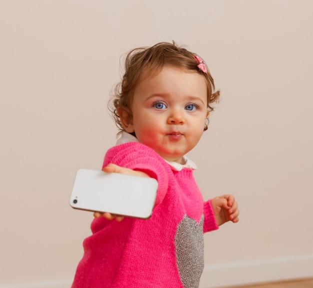 Petite fille joue avec un téléphone intelligent.