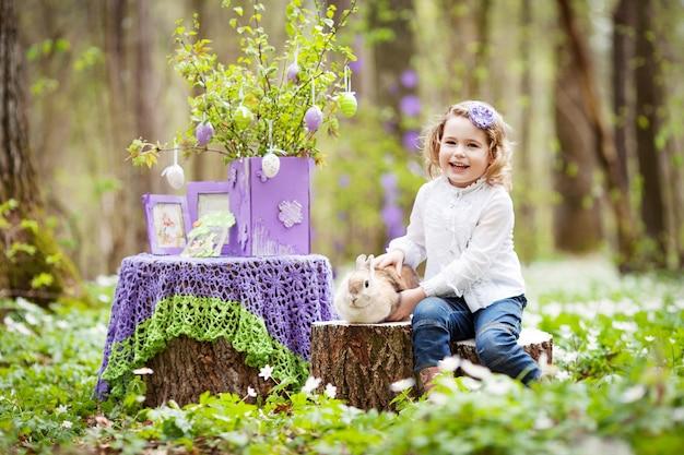Petite fille joue avec un vrai lapin dans le jardin. rire enfant à la chasse aux œufs de pâques avec lapin de compagnie. amusement extérieur printanier pour les enfants avec des animaux domestiques