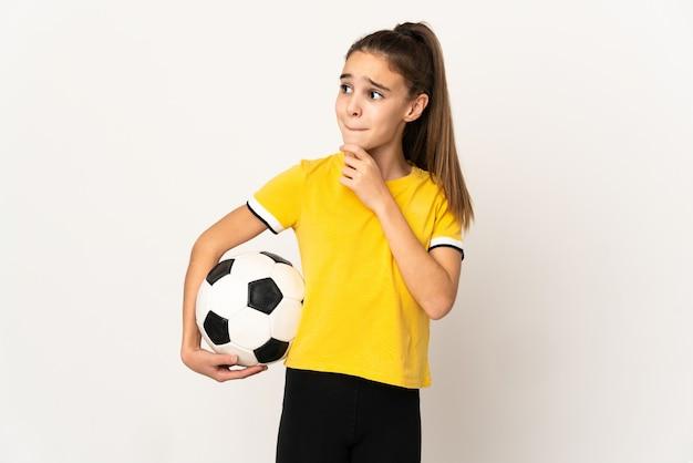 Petite fille de joueur de football isolée sur fond blanc ayant des doutes et pensant