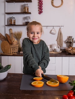Une petite fille joyeuse coupe une orange sur une planche et regarde la caméra