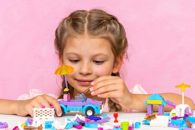 Petite fille joyeuse avec curiosité jouant dans le constructeur.