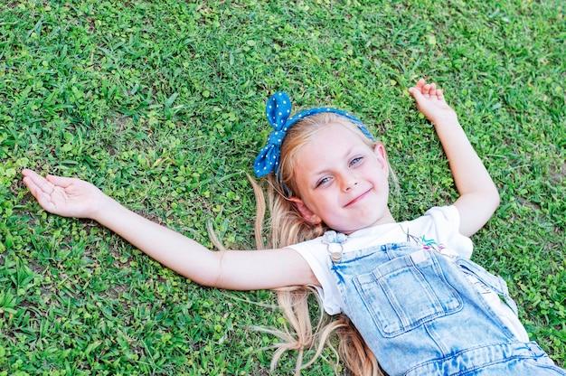 Petite fille joyeuse dans une combinaison en jean, allongée sur une herbe verte