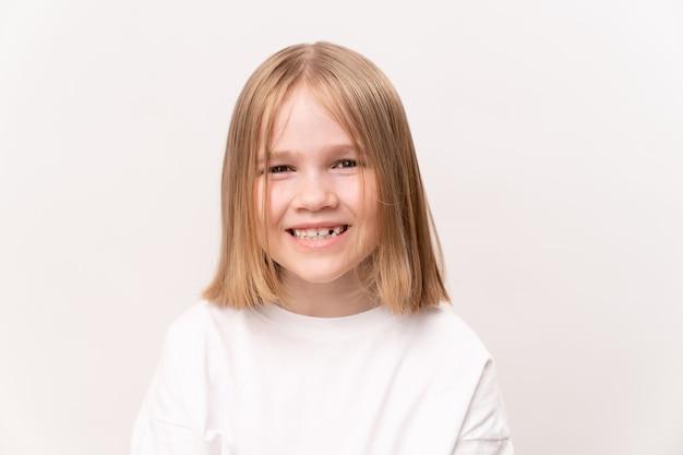 Petite fille joyeuse et heureuse avec une coupe de cheveux quad sur fond blanc. enfance heureuse. vitamines et médicaments pour l'enfant.