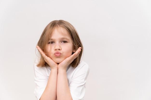 Petite fille joyeuse et heureuse avec un quad de coupe de cheveux tient les mains au visage sur un fond blanc. enfance heureuse.vitamines et médicaments pour l'enfant. faire un vœu et croire en un rêve