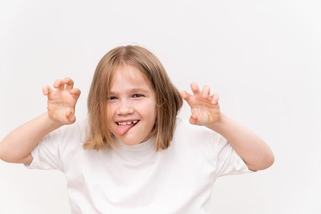 Une petite fille joyeuse et heureuse avec un quad de coupe de cheveux tient ses mains jointes devant le héron sur fond blanc. enfance heureuse. vitamines et médicaments pour l'enfant. faire un vœu et croire en un rêve