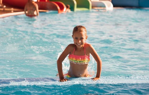 Petite fille joyeuse jouant dans la piscine avec de l'eau claire et claire et regardant en souriant à la caméra