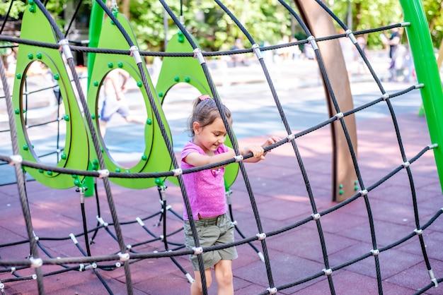 Petite fille joyeuse joue en vacances dans le parc sur le terrain de jeu l'enfant s'amuse dans la rue en vacances l'enfant fait du sport sur des simulateurs