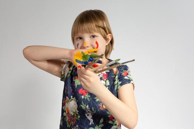 Une petite fille joyeuse avec de la peinture sur ses mains et son visage et ses pinceaux