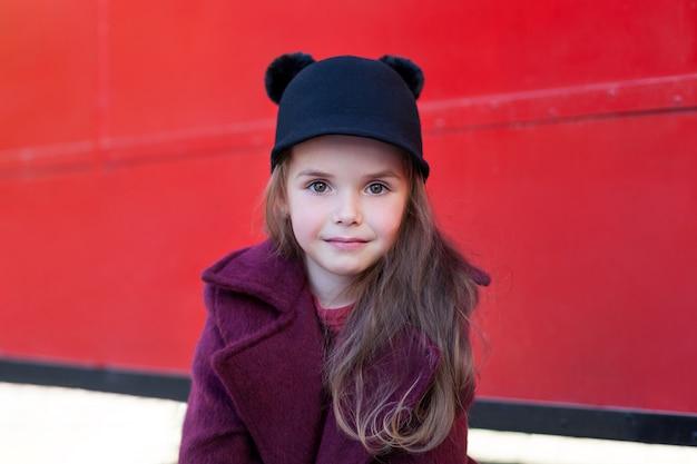 Petite fille joyeuse près du bus anglais rouge dans un beau manteau et un chapeau. petite fille gaie près du bus anglais rouge dans un beau manteau et un chapeau. le voyage de l'enfant. bus scolaire. bus rouge de londres.