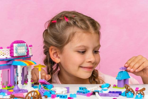 Une petite fille joyeuse recueille un constructeur de couleurs à partir de cubes.