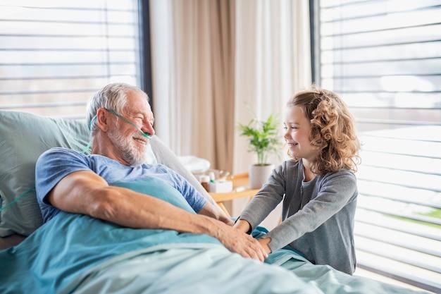 Une petite fille joyeuse visitant un grand-père malade au lit dans une chambre d'hôpital.