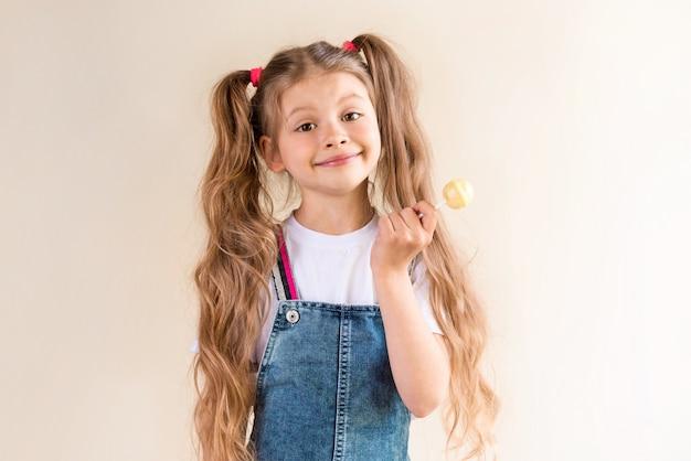 Une petite fille en jupe en jean tient une sucette.
