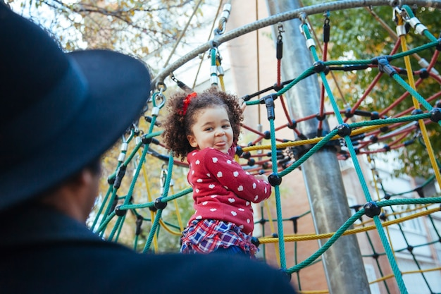 Petite fille avec la langue hors de sa bouche, jouer à des jeux à l'extérieur