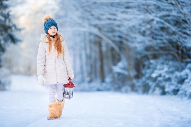 Petite fille avec lanterne dans la forêt gelée le soir de noël