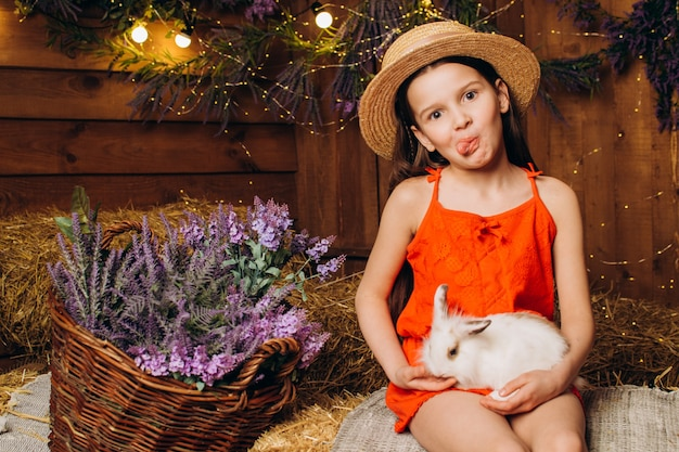 Petite fille avec un lapin dans une ferme sur fond de foin et de lavande