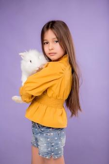 Petite fille avec lapin de pâques sur fond violet