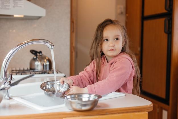 Petite fille lavant la vaisselle dans la cuisine d'une caravane