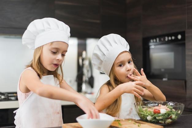 Petite fille léchant son doigt pendant que la soeur mélange de la nourriture dans un bol