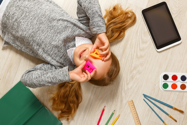 Petite fille avec les lettres a et b gisant sur le sol.