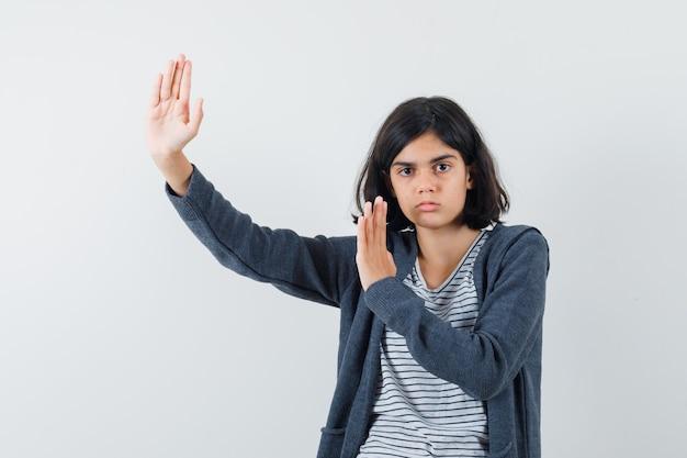 Petite fille levant les mains pour se défendre en t-shirt, veste et air confiant.