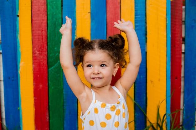 Une petite fille lève les mains debout près d'une clôture multicolore en bois