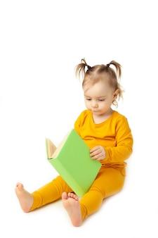 Petite fille lisant isolé sur blanc. bébé mignon avec livre.