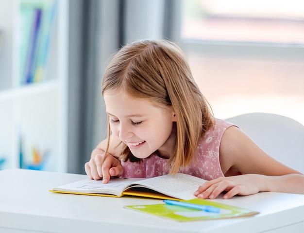 Petite fille lisant un livre au bureau en classe