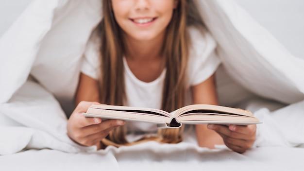 Petite fille lisant un livre au lit