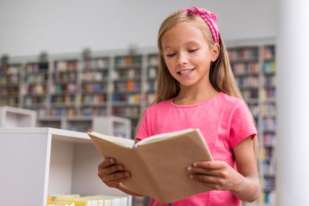 Petite fille lisant un livre dans la bibliothèque