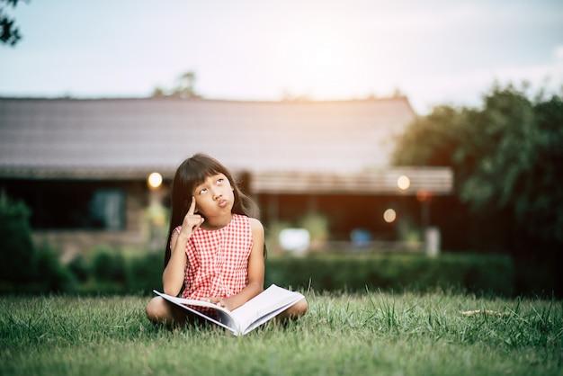 Petite fille lisant un livre dans le jardin de la maison