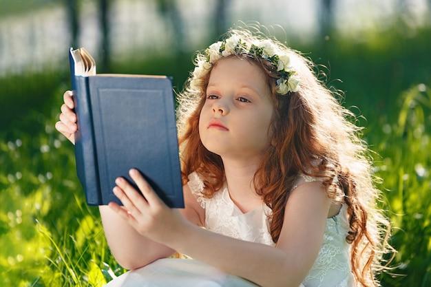Petite fille lisant un livre dans le parc