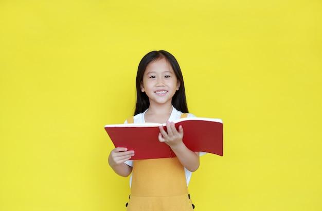 Petite fille lisant un livre sur fond jaune