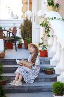Petite fille lisant un livre sur les marches de l'enfant de la maison apprend des leçons après l'école